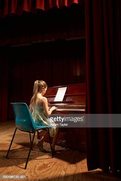 Girl (9-11) playing piano on stage, rear view from wings