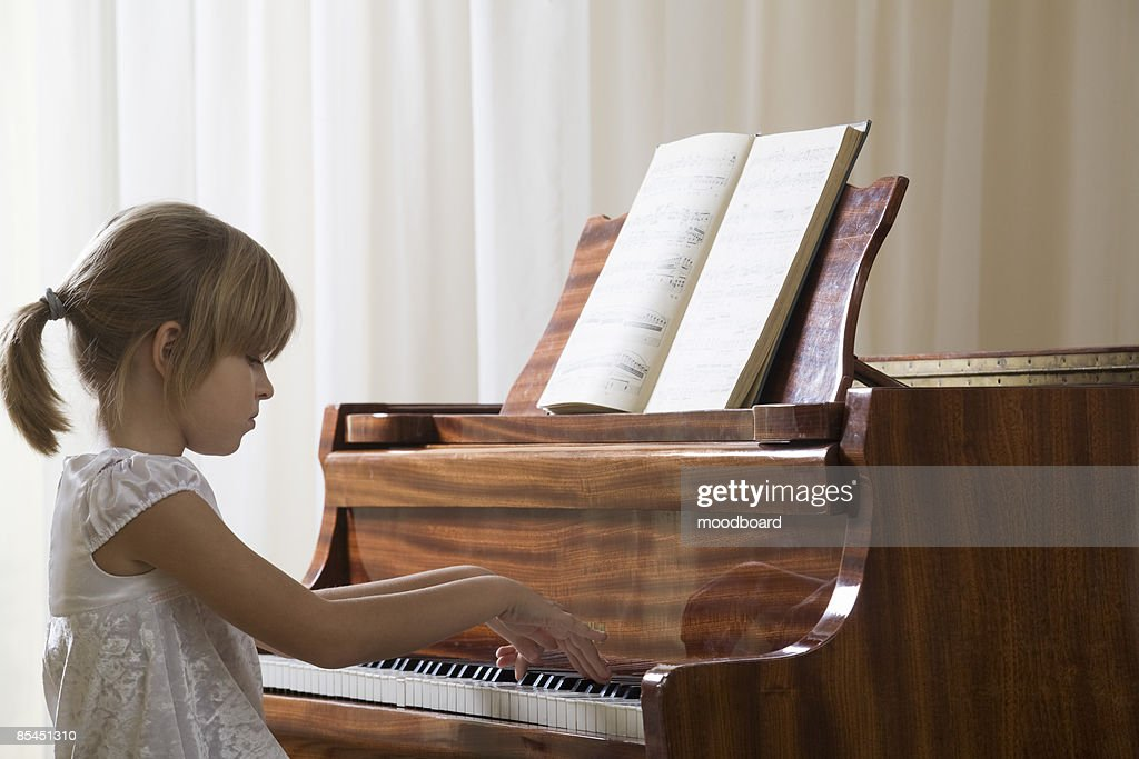 Girl (5-6) playing piano : Foto de stock