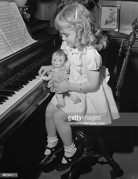 Girl playing piano with doll