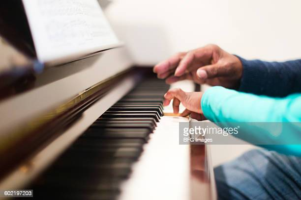 Girl (6-7) playing piano with grandfather, Cape Town, South Africa