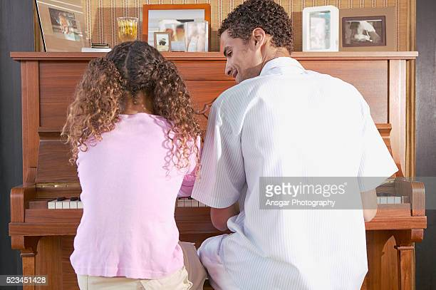 Girl playing piano with her father