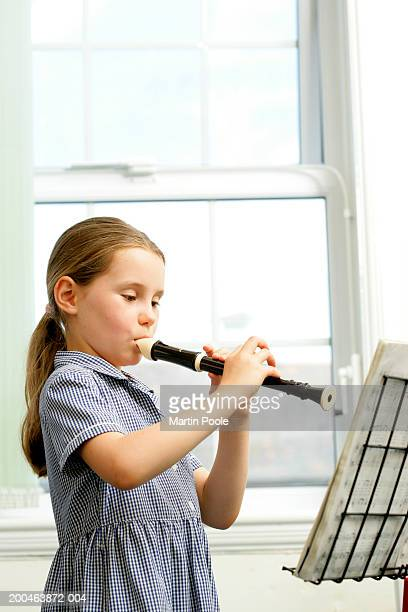 girl (6-8) playing recorder and reading music - recorder musical instrument stock photos and pictures