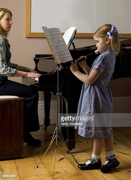 girl playing recorder and teacher playing piano - recorder musical instrument stock photos and pictures