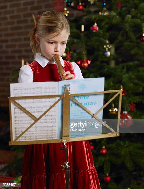Girl Playing Recorder in Front of Christmas Tree