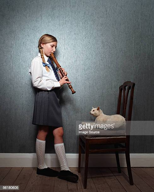 girl playing recorder to cat - recorder musical instrument stock photos and pictures