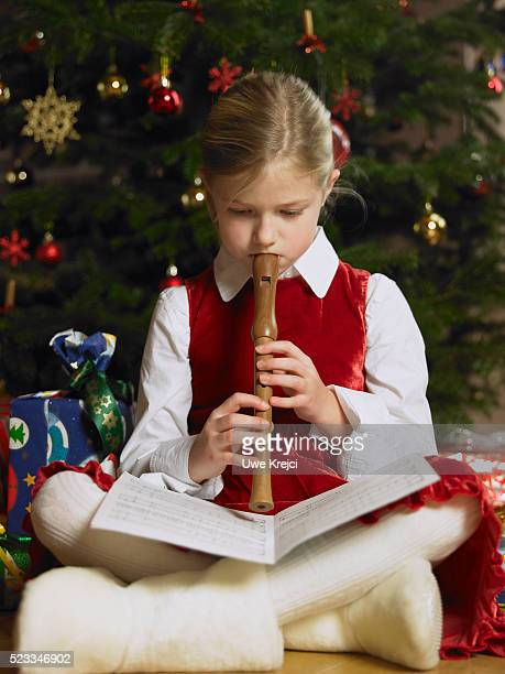 Girl Playing Recorder Under Christmas Tree