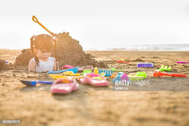 Girl playing sand on beach