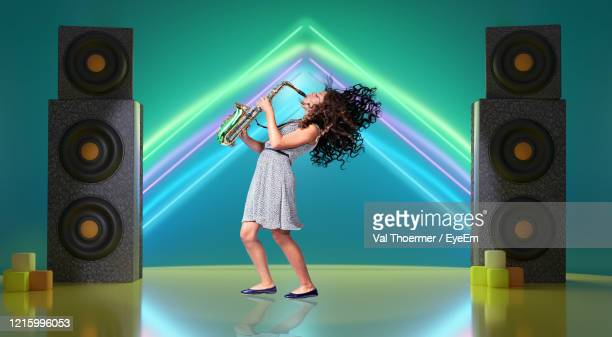 girl playing saxophone while standing against illuminated wall - val thoermer stock-fotos und bilder