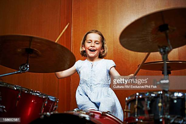 Girl playing set of drums