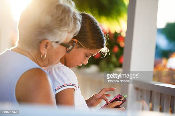 Girl playing smartphone game sitting on grandmothers lap in porch at sunset