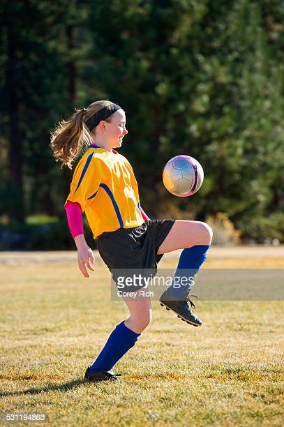A girl playing soccer in uniform.