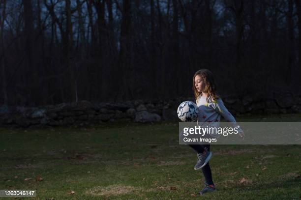 girl playing soccer outside at night - sporting term stock pictures, royalty-free photos & images