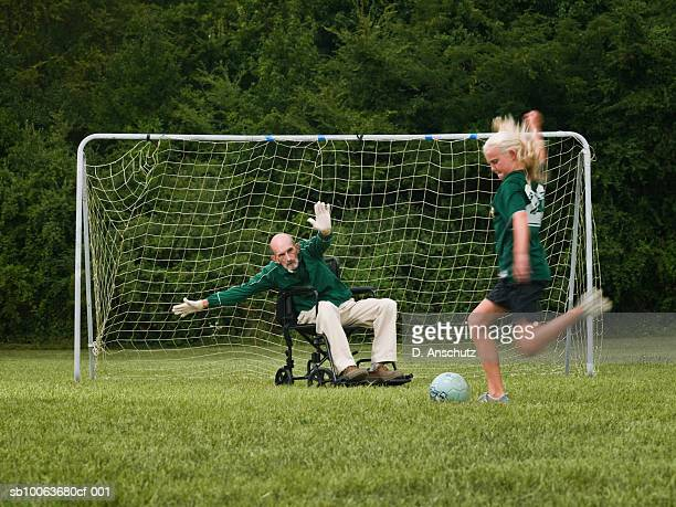Girl (10-11) playing soccer with grandfather in wheelchair as goal keeper