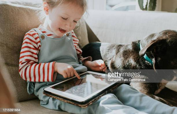 girl playing tablet device - lockdown stock pictures, royalty-free photos & images