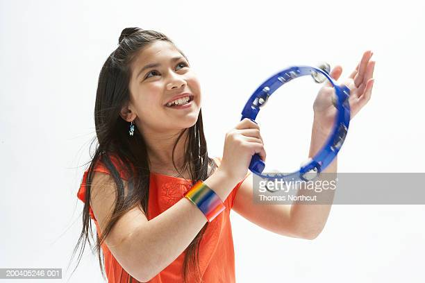 Girl (9-11) playing tambourine, looking up, smiling