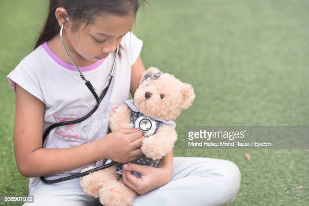 Girl Playing Teddy Bear In Lawn