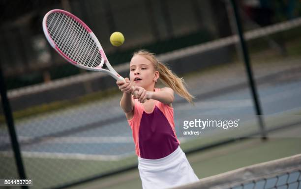 girl playing tennis and hitting a ball with the racket - tennis stock pictures, royalty-free photos & images