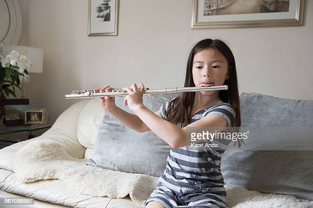 Girl playing the flute on sofa
