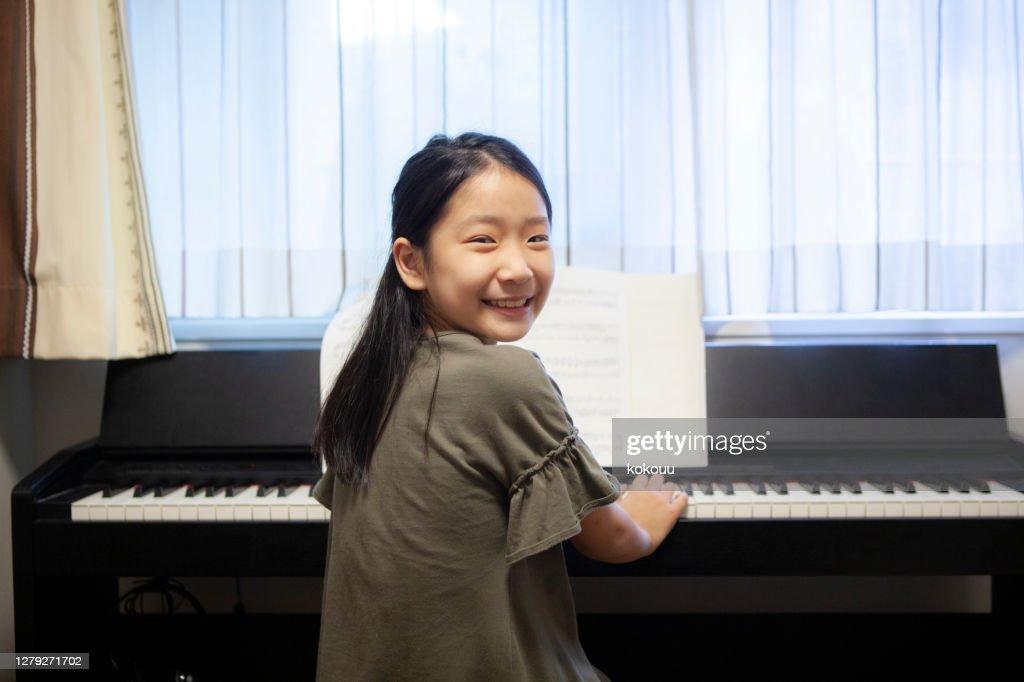 楽しそうにピアノを弾く女の子 : ストックフォト