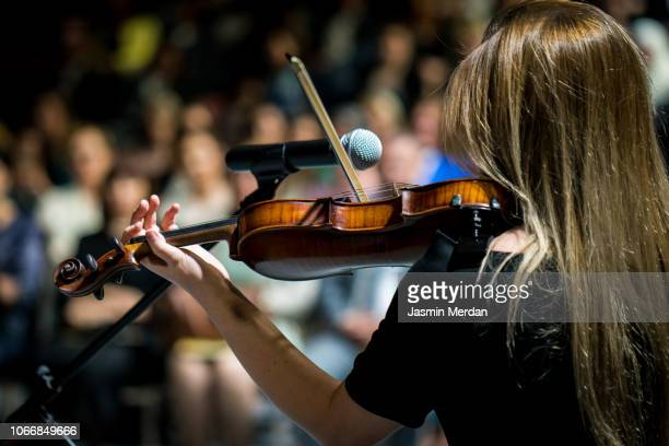 girl playing the violin in concert hall - audition stock pictures, royalty-free photos & images