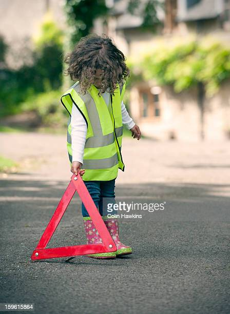 Girl playing traffic worker on rural road