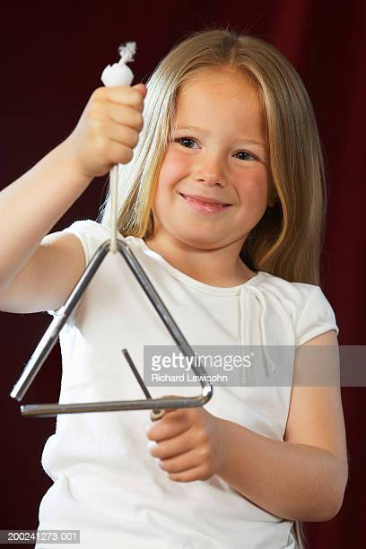 girl (4-6) playing triangle, smiling, close-up - triangle percussion instrument stock photos and pictures