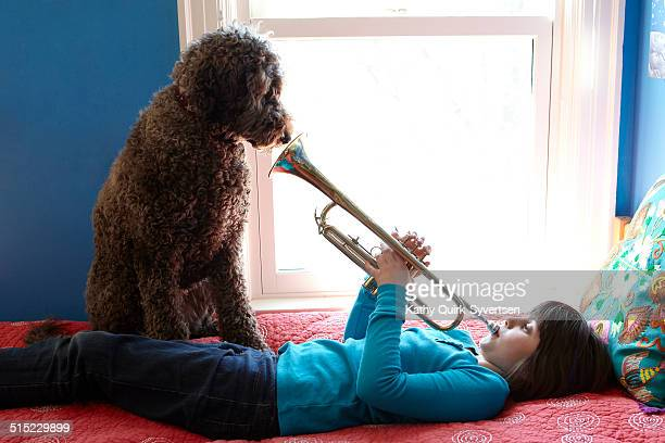Girl playing trumpet for dog, in front of window