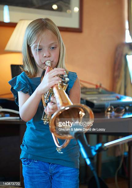 girl playing trumpet into microphone - saint ferme stock photos and pictures