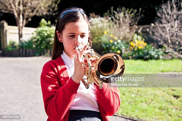 Girl playing trumpet, school uniform, garden