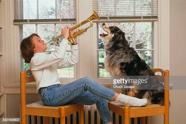 Girl playing trumpet to dog