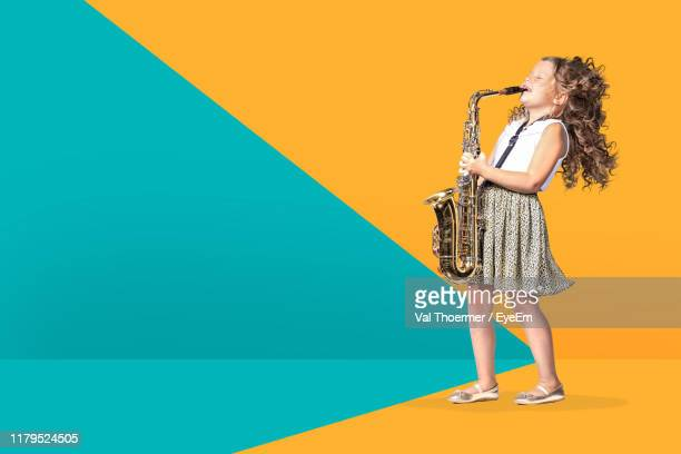 girl playing trumpet while standing against colored background - zweifarbig farbe stock-fotos und bilder