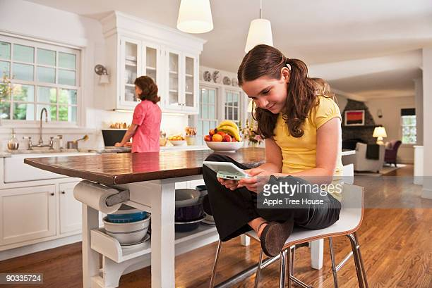 girl playing video game in kitchen - handheld video game stock pictures, royalty-free photos & images