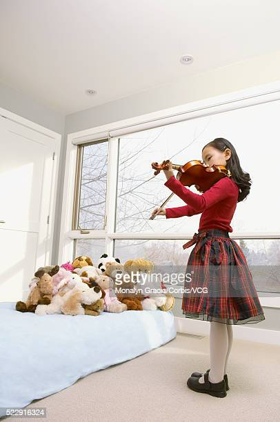 Girl playing violin concert for her stuffed animals