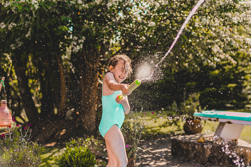 girl  playing water gun fight at poolside - gettyimageskorea