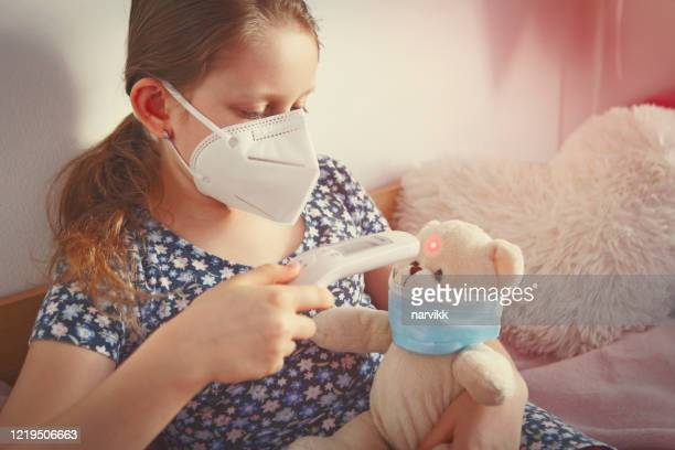 girl playing with a bear toy in quarantine - cute nurses stock pictures, royalty-free photos & images