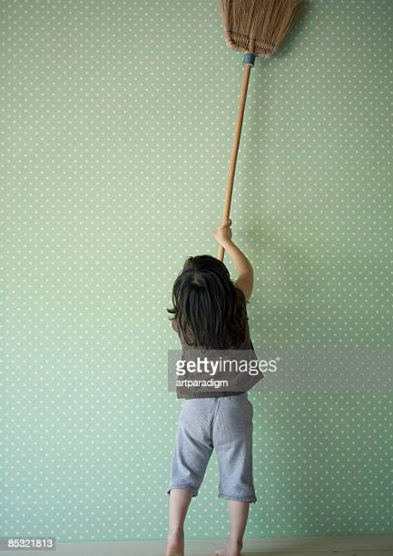 A girl playing with a broom
