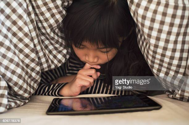 girl playing with a digital tablet in bedroom - leisure games ストックフォトと画像