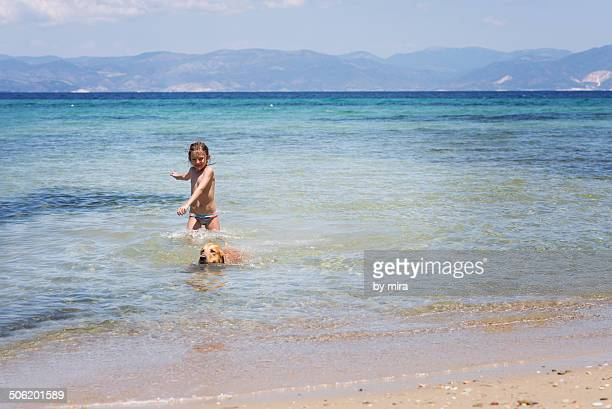 Girl playing with a dog in the sea