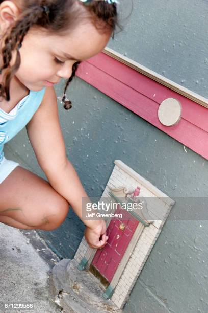 A girl playing with a fairy door on Main Street