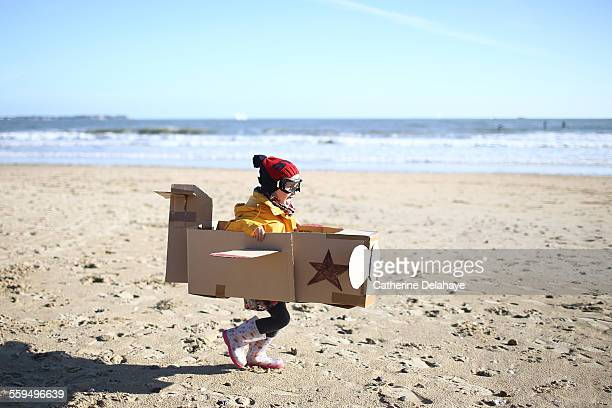 A girl playing with a plane on the beach