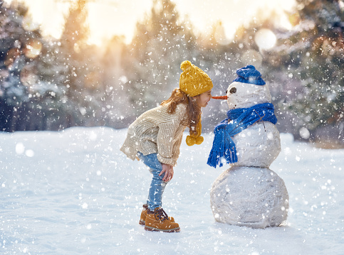 girl playing with a snowman 499910260