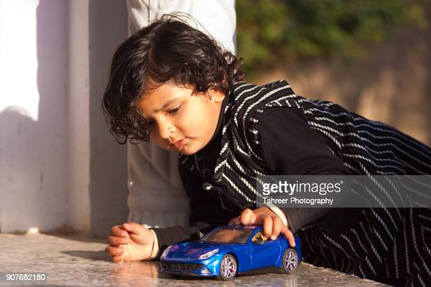 a girl playing with a toy car - cute pakistani boys stock photos and pictures