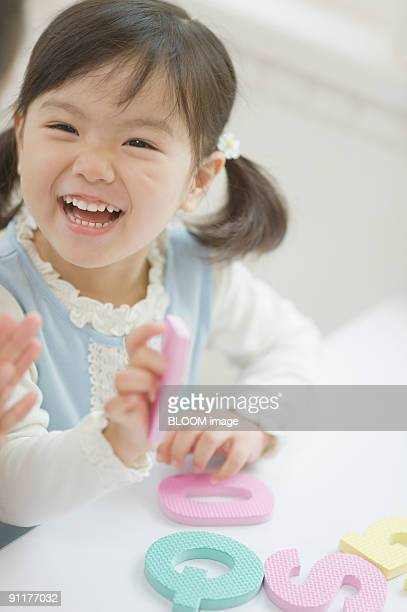 Girl playing with alphabet mats, smiling
