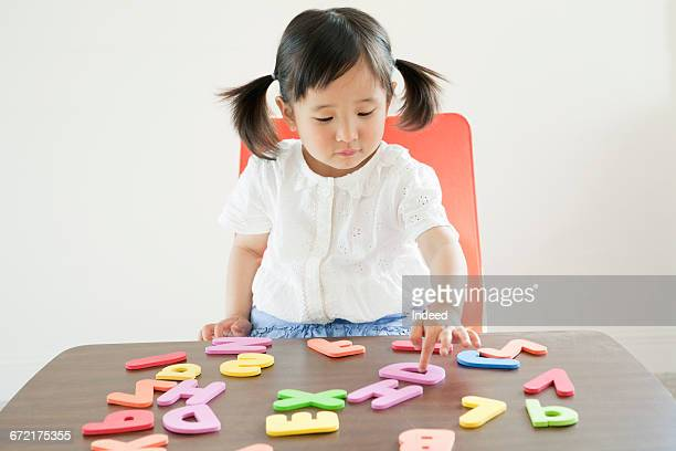 Girl playing with alphabet toy