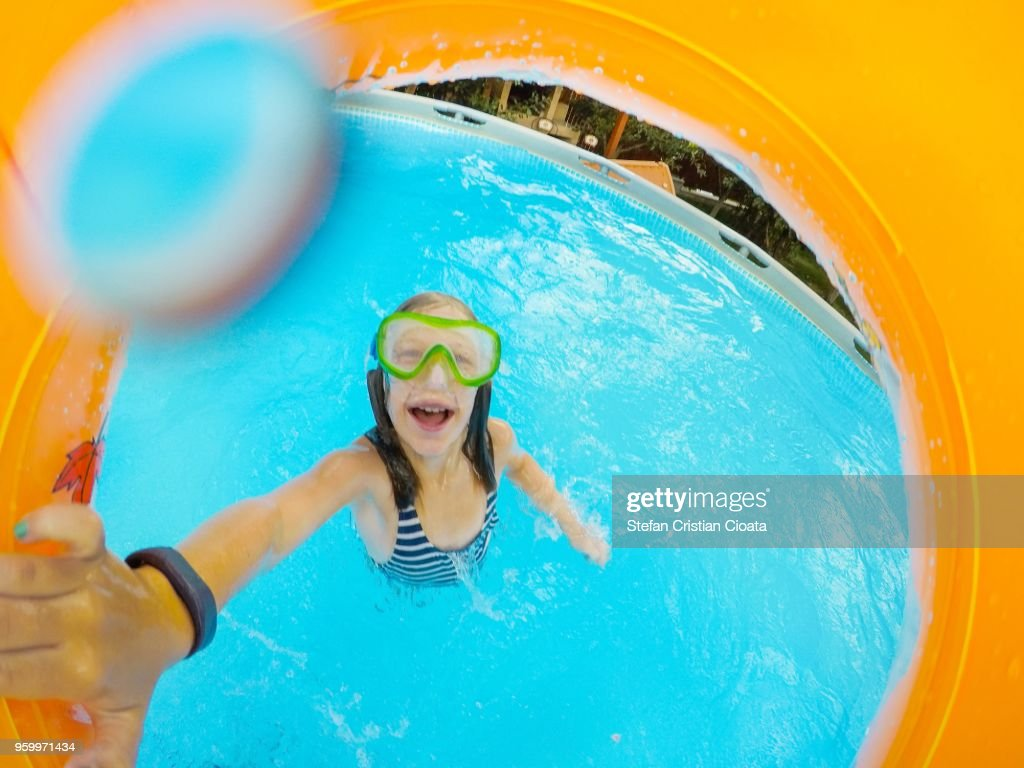 Girl playing with an orange inflatable ring in the pool : Stock-Foto