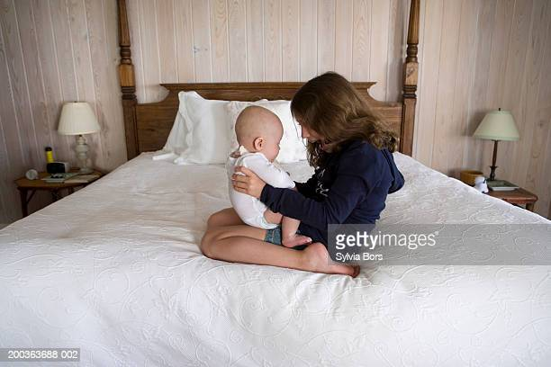 Girl (6-8) playing with baby brother (3-6 months) on bed, side view