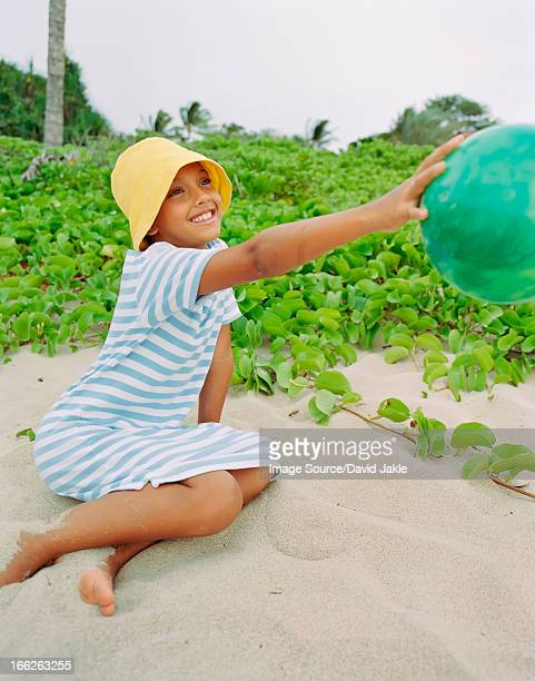 Girl playing with ball on beach