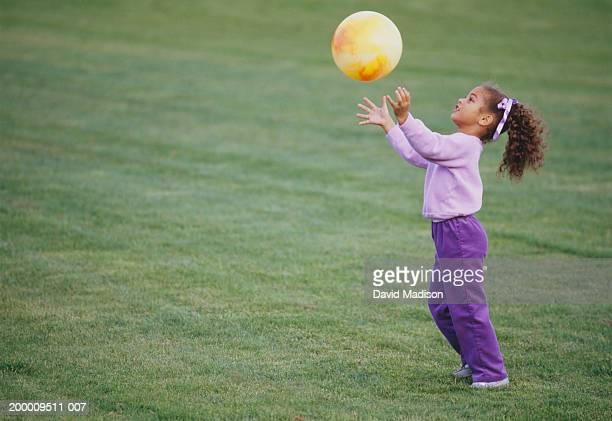 girl (4-6) playing with ball on field, side view - attraper photos et images de collection