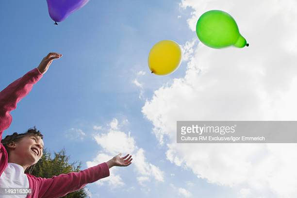 Girl playing with balloons outdoors