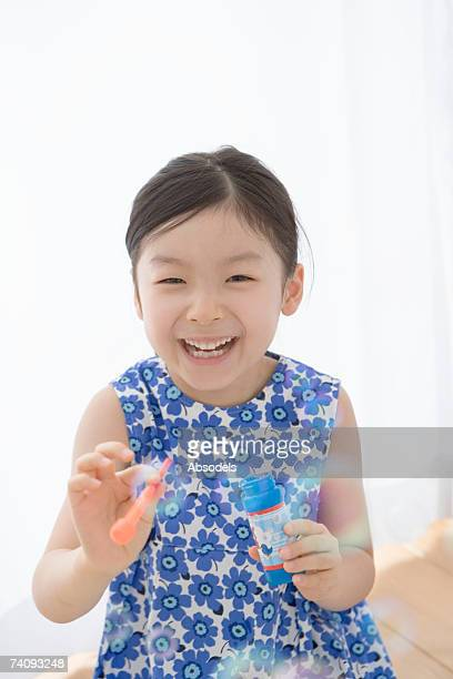 Girl playing with bubbles in bathroom, Smiling